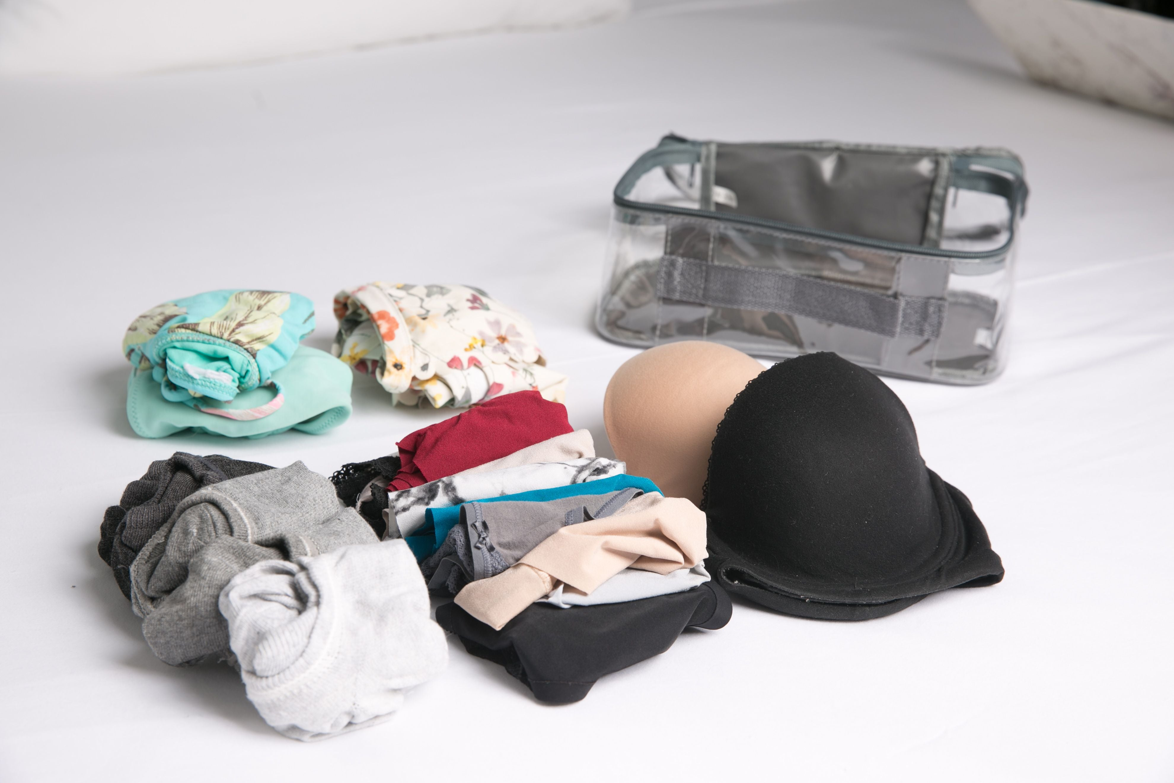 Undergarments rolled beside small packing cube