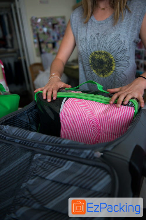 Stack the packing cubes vertically in the suitcase to maximize space.