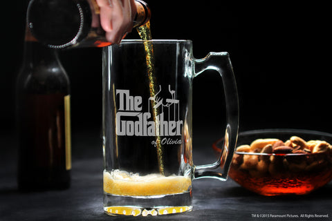 Personalized beer mug for godmother and godfather filled with beer next to bowl of nuts and lady pouring bottle of beer