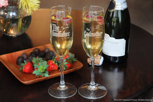 Two Personalized Godparent Champagne flutes with champagne and strawberries