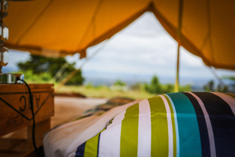 Luxury inside a glamping bell tent with the ground sheet unzipped and the sides rolled up