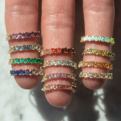 slid gold birthstone rings on a hand for every month