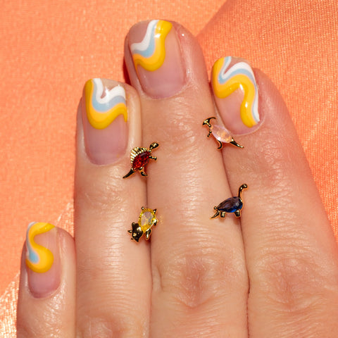 dinosaur earrings in between fingers with colorful nail art