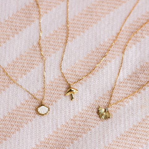 three solid yellow gold necklaces in the shape of a mushroom, shell, and ginkgo leaf