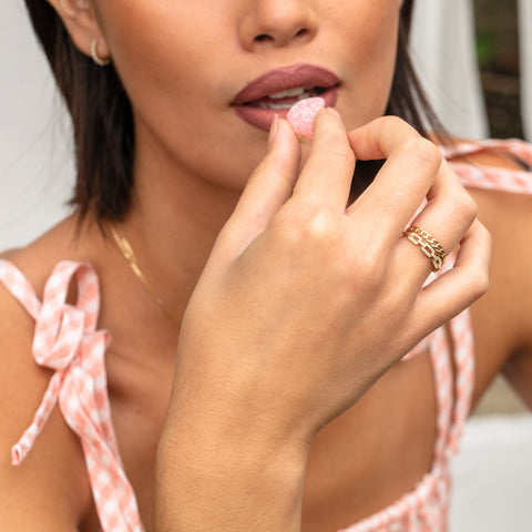 solid gold chain rings on a hand eating a piece of candy