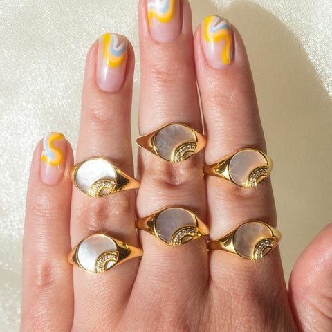 mother of pearl yellow gold rainbow signet rings on a hand