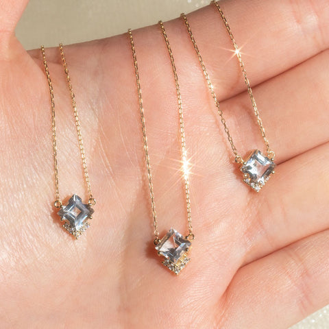 topaz and diamond solid gold dainty pendant necklaces in a hand