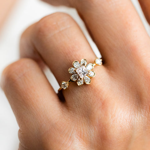 unique flower diamond engagement ring on a hand