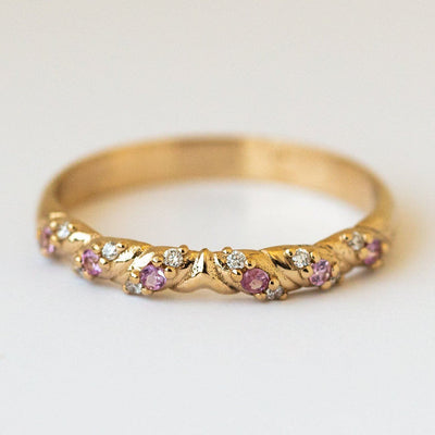 solid yellow gold saturn's garland ring with diamonds and pink sapphire