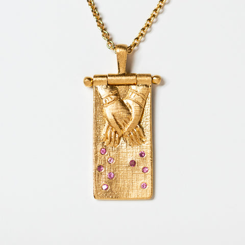 pink tourmaline hand holding necklace pendant unique yellow gold jewelry