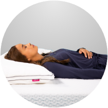 Woman sleeping on her back on an Endy Mattress and Pillow.