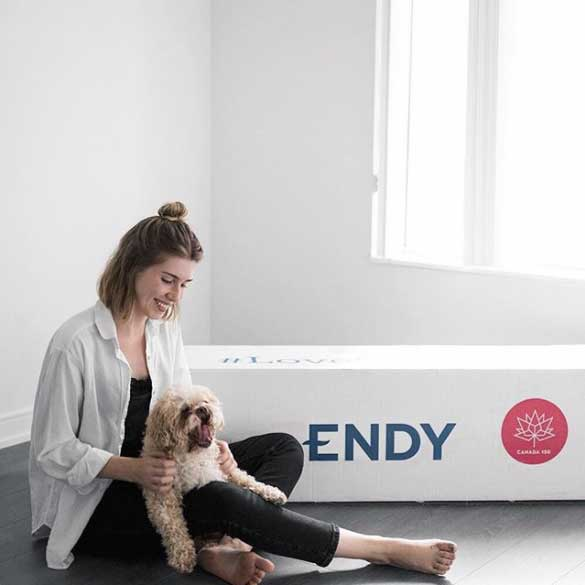 Woman petting her dog next to Endy Mattress box