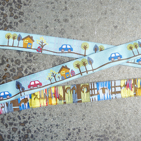 sue spargo ribbon tooting along cars houses blue