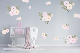 Pastel pink illustrated flowers with green leaves on a grey wall in a child's nursery with a white crib.