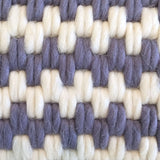 Detail view of artisan made hand-stitched textured pillows in lavender stripe. Wool and linen.