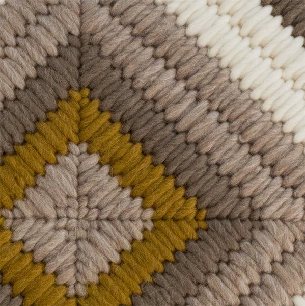 Detail view of textured hand stitching on Ochre Diamond throw pillow.