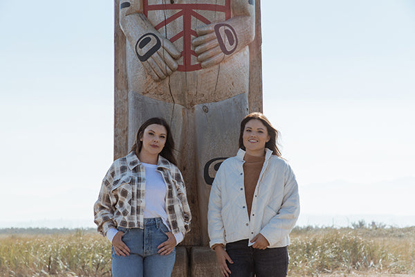 Candace and Ashley standing at the base of totem pole on K'omoks First Nation