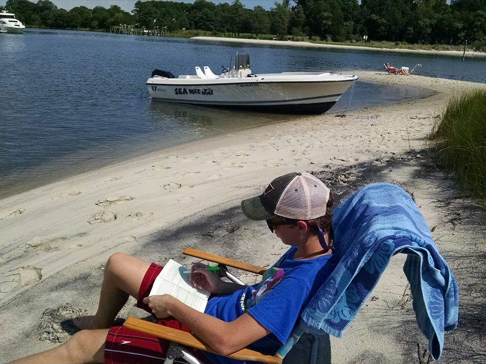 Reading on the Beach with Boat in Background