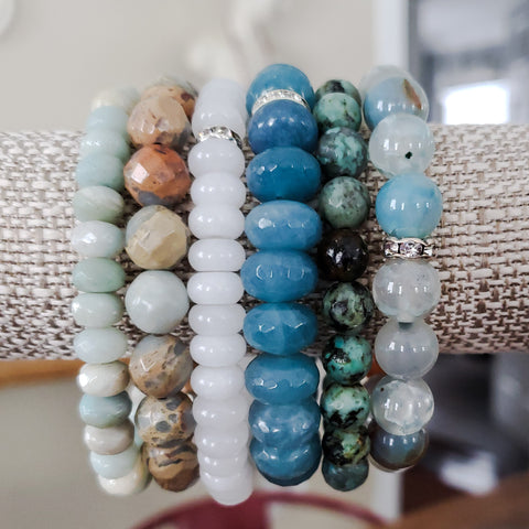 collection of 6 beaded stone bracelets from pale to deep blue