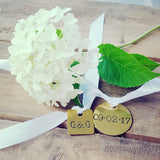 vintage hand stamped wedding dates on brass tags tied on a white ribbon