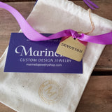 vintage hand stamped messages on brass tags tied on a purple ribbon
