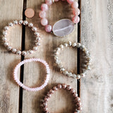 Cherry Blossom stack of stretch bracelets on wrist in rose golds and quartz