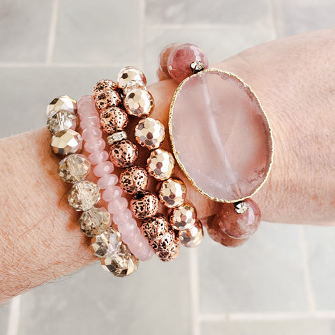 stack of Rose colored metallic Protection Bracelets on a wrist
