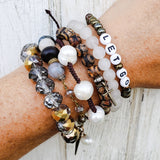 stack of six protection bracelets on a wrist including the thin adjustable cultured freshwater pearl cord bracelet