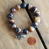 madagascar swirl agate protection bracelet elephant nose up charm and M tag penny for size reference
