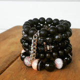 protection bracelets by Marinella five stacked high stone and crystal 12mm - 14mm beads sizes all in dark black tones one with a touch of pink quartz