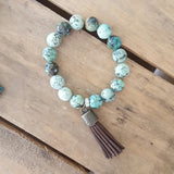 "protection bracelet by Marinella jewelry 12mm turquoise agate w 2"" long brown ultra suede and brass tassel"
