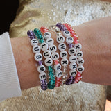 stack of bracelets 6mm beads & letter beads each with a loving word