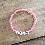 6mm pink Czech beads round white beads w black letters XOXO bracelet