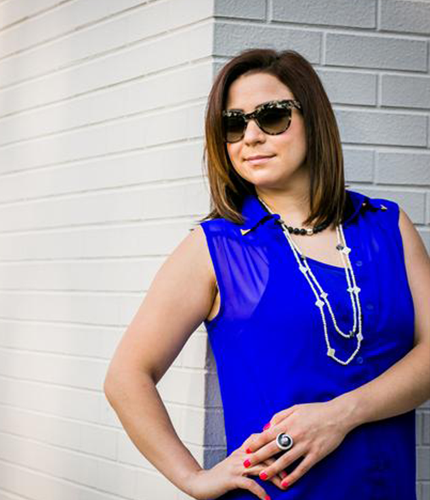 A woman in a bright blue shirt, wearing multiple necklaces and rings.