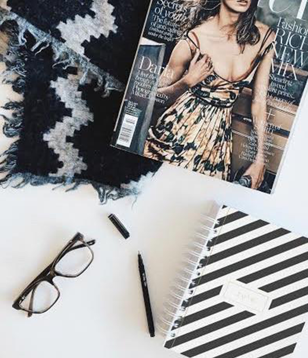 A magazine and journal laying beside a pair of reading glasses and a pen.
