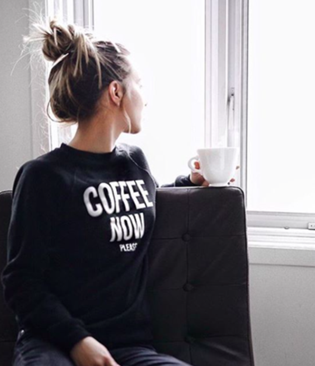 A woman sitting in a chair with a cup of coffee, wearing a sweatshirt that says 'Coffee Now Please'.