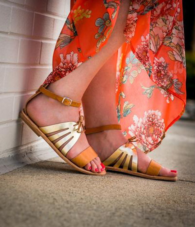 Close up of a person's feet wearing gold, strappy sandals.