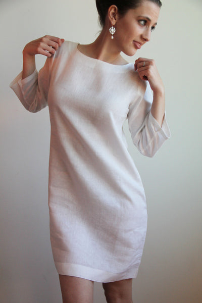 "The most popular of Guru's linen dresses, the Classic Shift features 3/4 length sleeves, a square hem, and an elegant boat-neck design. This linen has a very breathable waffle weave design, with silver or gold threads, interwoven.    Length: 36""  Made out of 100% European Linen. Dry Clean Only.  Available in: Ivory waffle weave linen with silver thread and Ivory waffle weave with gold thread. Dry Clean Only.  Image show in White linen."
