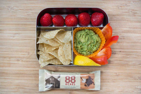 Nut-free lunch with strawberries, tortilla chips, guacamole, bell peppers, 88 acres seed bar. Great snack and lunch for kids.