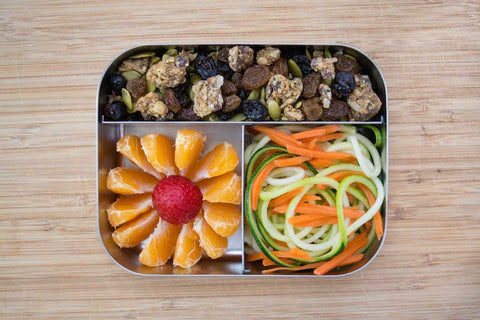 Lunch box with orange slices, spiralized vegetables, chocolate  seednola trail mix. Great nut-free option for back-to-school.