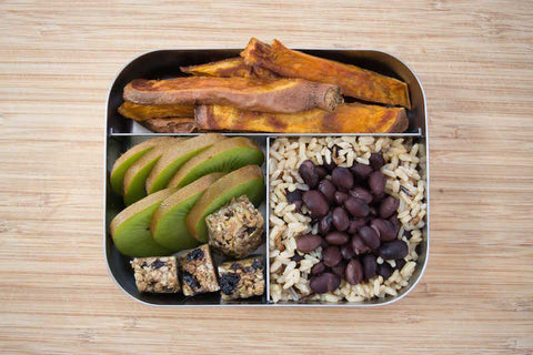Lunch box with brown rice and black beans, sliced kiwi and Triple Berry seed bar, sweet potato fries. Quick lunch idea for kids.