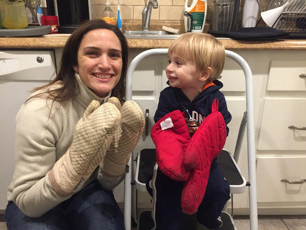 Nicole and Emmett cooking in the kitchen, both wearing oven mitts