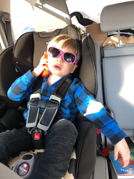 Emmett wearing sunglasses and on his phone in his carseat