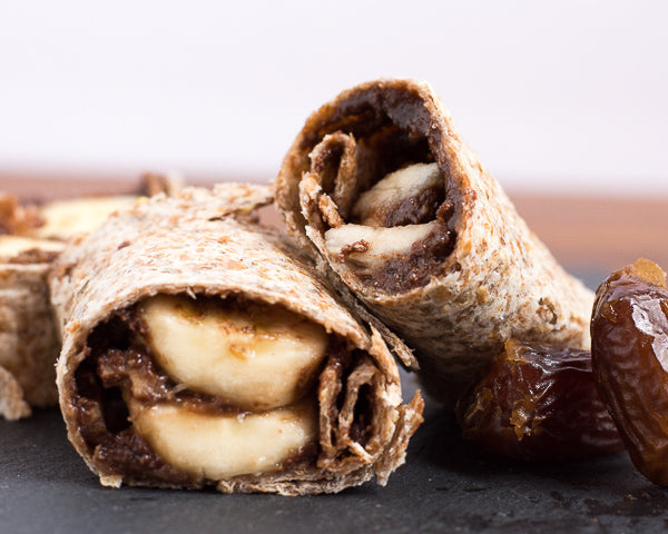 Sliced banana, dates, and dark chocolate sunflower seed butter wrapped in a tortilla. Healthy dessert option or fuel for student athletes.