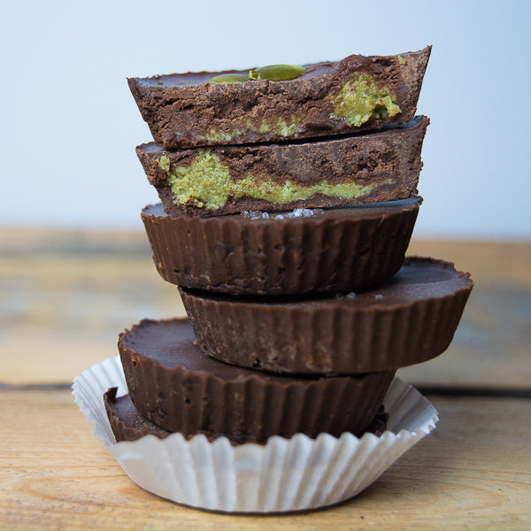 Stack of nut-free, pumpkin seed butter dark chocolate cups. Easy, home-made Halloween treats.