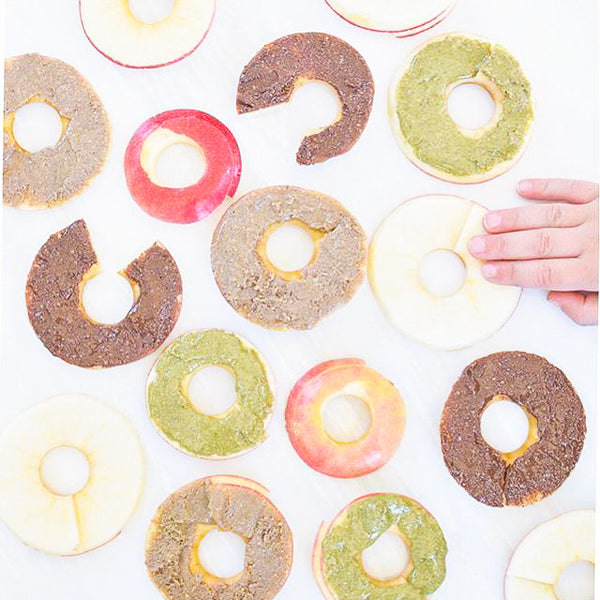 Sliced apple rounds covered in seed butter are the new healthy donuts. Topped with seed butter, chocolate chips, dried fruit, or Seednola.