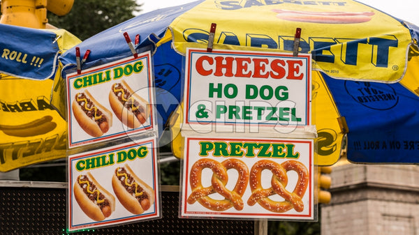 hot dog vendor umbrella - pretzels, cheese and chili dogs on sunny day