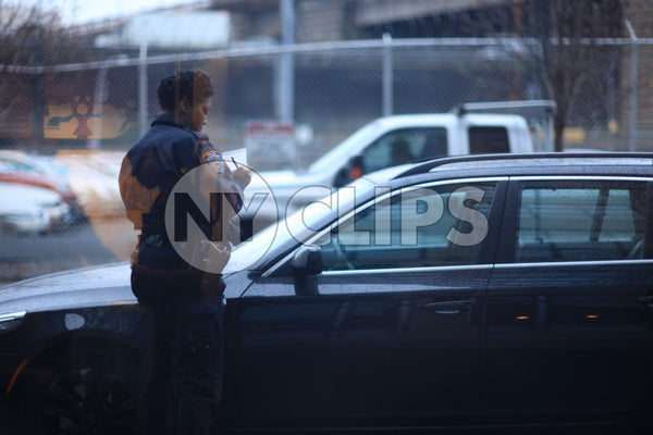 female police officer writing ticket on car windshield - NYPD cop giving summons