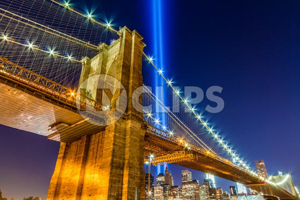 Brooklyn Bridge at night with 911 beams over Manhattan skyline, upward angle under beautiful evening sky with lights