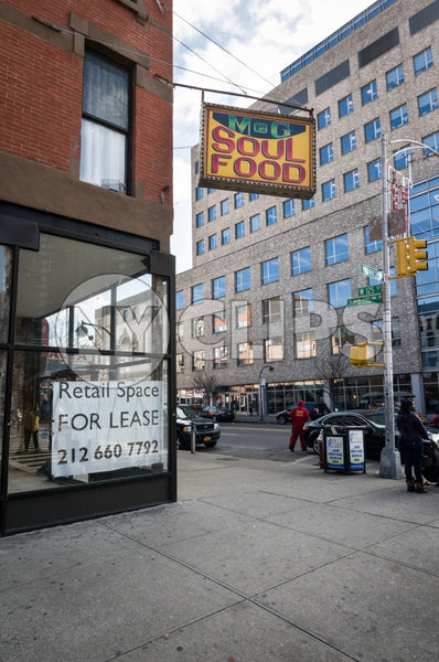 Harlem soul food restaurant with retail space for lease sign on corner - Uptown Manhattan during day